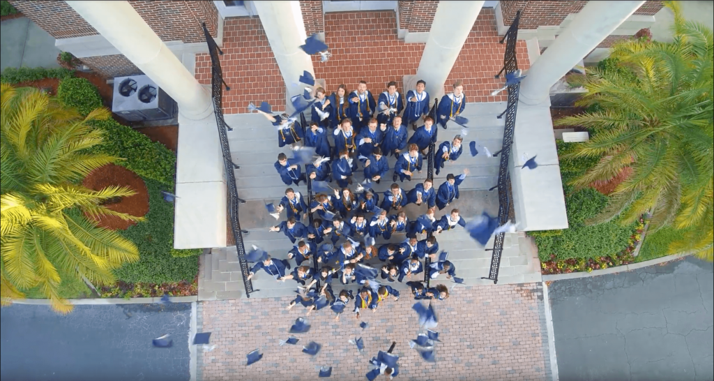 Aerial View of Foundation Academy Graduates Throwing Their Graduation Caps Into the Air